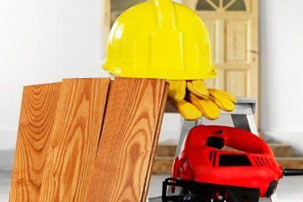 un elmetto una sega e delle assi di legno