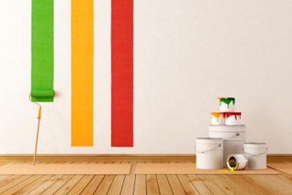 dei secchi di vernice e un muro a strisce colorate