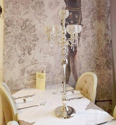 tavolo con candelabro di cristallo con perline, sedie beige e vista di un dipinto sulla parete raffigurante una donna che volteggia