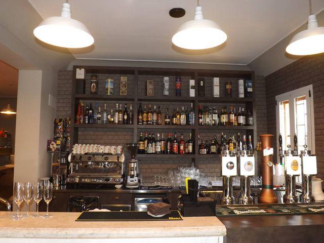 vista della zona bar con bancone,macchina del caffe,liquori esposti, bicchieri e rubinetti per birre alla spina
