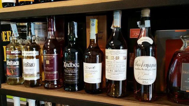 bottiglie di liquori viste da vicino su mensole in legno
