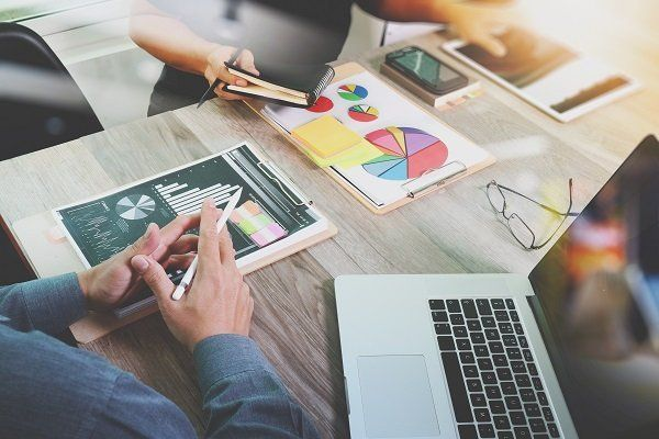 due mani con una penna e una scrivania con dei fogli con dei grafici disegnati