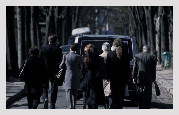 people walking behind the funeral van