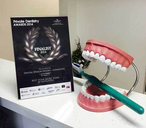 private dentistry awards diploma with a blueprint of human teeth holding a toothbrush thropy