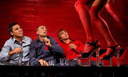 Tre uomini seduti in fila mentre guardano una donna con lingerie rossa e tacchi alti che balla su un tavolo