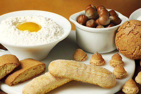 nocciole,savoiardi, amaretti,cantuccini e una ciotola con farina e uovo