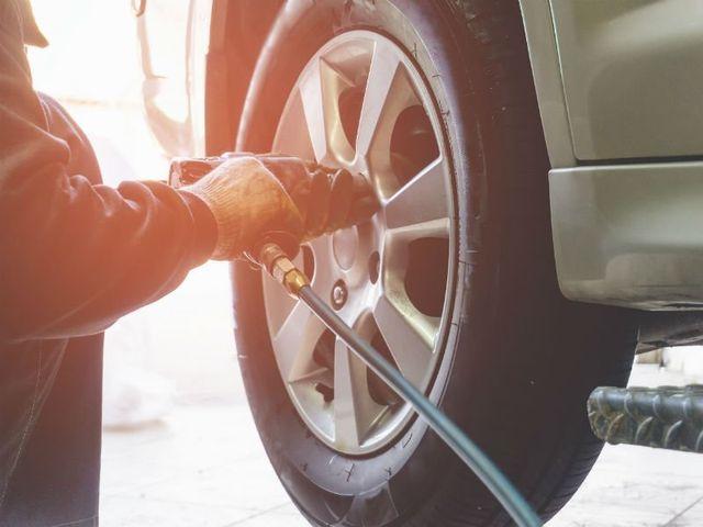una ruota è una mano con un trapano che svita un bullone