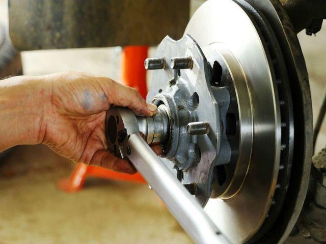 una mano con un attrezzo che smonta un disco di un freno