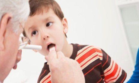 medico controlla la gola di un bambino