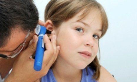 medico controlla l`udito a una bambina