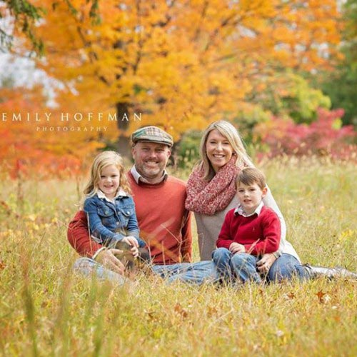 family sitting in field in fall nurturing children and building families in roseville ca