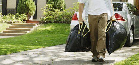 man walking with garbage bags