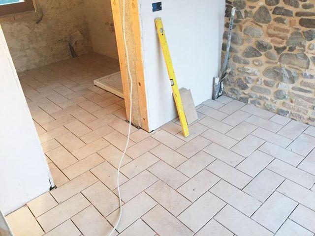 un pavimento piastrellato di color bianco e una livella gialla appoggiata al muro