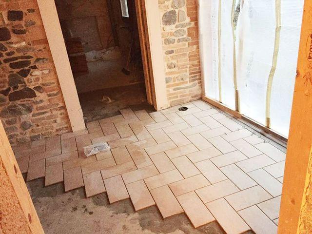 un appartamento in fase di ristrutturazione con il pavimento con delle piastrelle non ancora del tutto posizionate