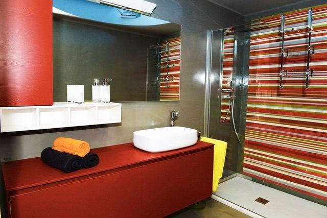 un bagno moderno con vista di un lavabo e sotto un mobile bordeaux