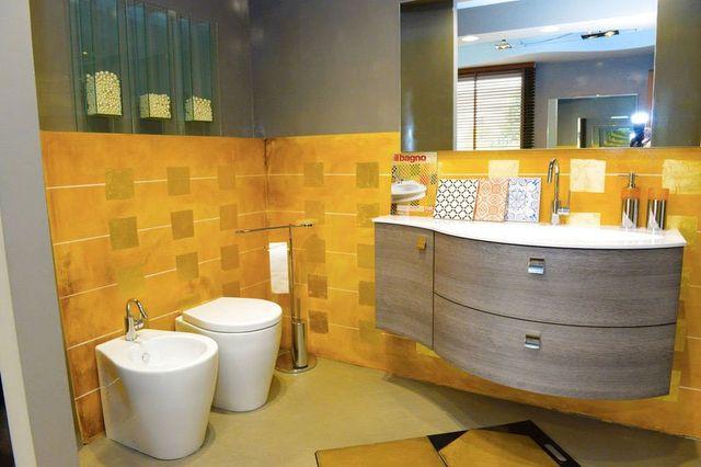 un bagno con muri color giallo, sulla sinistra un wc e un bidet e al centro un lavabo