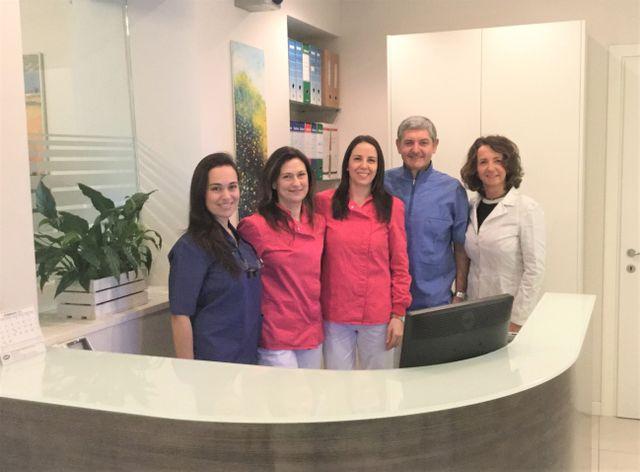 quattro donne e un uomo, lo staff dello Studio Brutti, dietro un bancone di una reception di uno studio