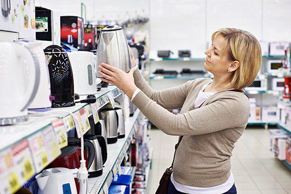 una donna con in mano un bollitore e affianco altri elettrodomestici su uno scaffale all'interno di un negozio
