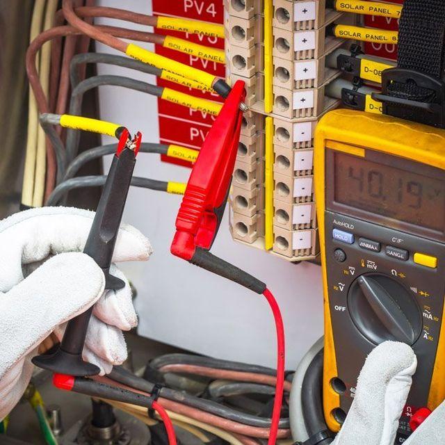Addetto mentre misura la potenza di funzionamento di un impianto elettrico