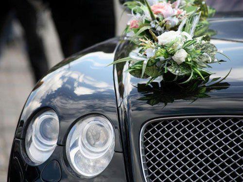 Carro funebre con ghirlanda di fiori sul cofano