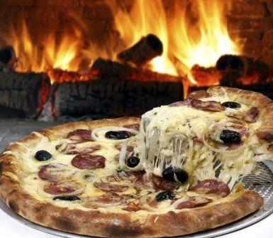 pezzo di pizza con mozzarella filante vicino a un camino