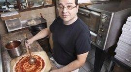 pizzaiolo mentre mette del pomodoro sulla pasta della pizza