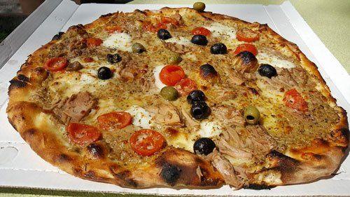 una pizza con olive nere, verdi e pomodorini