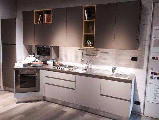 una cucina angolare in legno con mobili bianchi
