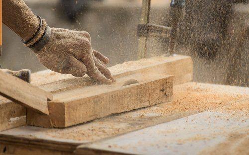 operaio segando un pezzo di legno