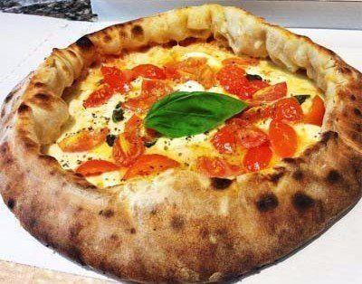pizza con spicchi di pomodoro e foglia di basilico