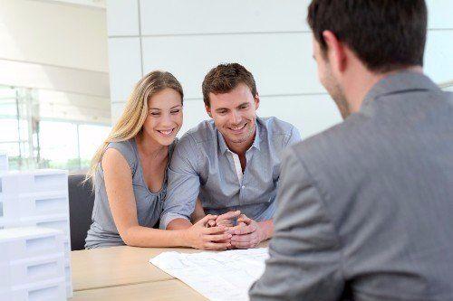 una coppia seduta alla scrivania di un'agenzia immobiliare