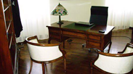 una scrivania in legno con due sedie e una poltrona nera