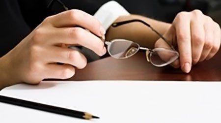 due mani che tengono degli occhiali da vista