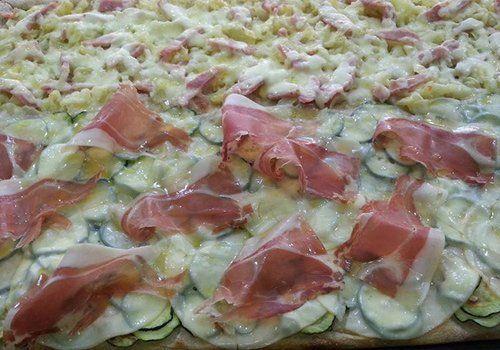 pizza due gusti con prosciutto zucchine formaggio e carciofi