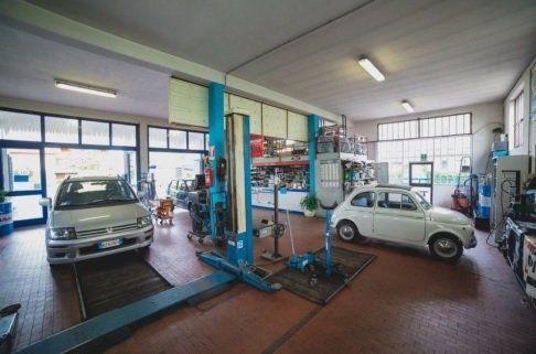 Interno del laboratorio con un'auto in riparazione e un altro già riparato