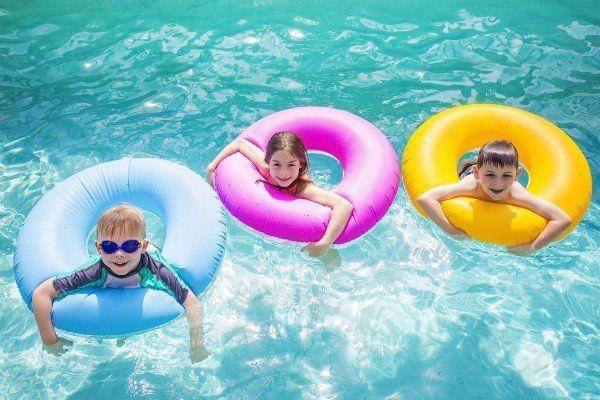 Tre bambini nell'acqua con salvagente