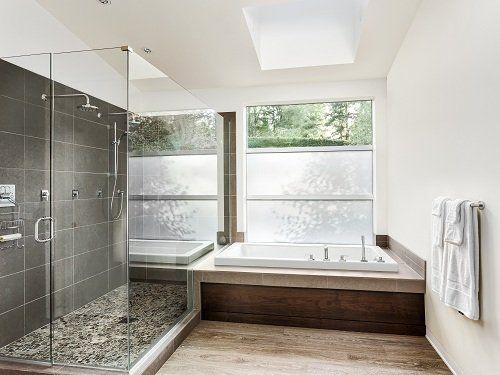 un bagno con una vasca e un box doccia in vetro