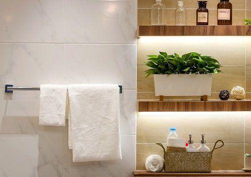 un portasciugamani con degli asciugamani e delle mensole con olii essenziali e altro