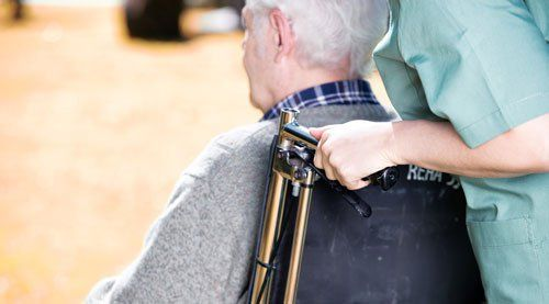 un'infermiera che spinge la sedia a rotelle di un signore anziano