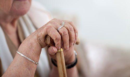 le mani di una signora anziana appoggiate su un bastone