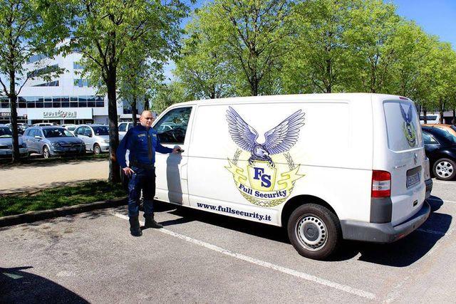 Uomo della sicurezza di fianco a furgoncino bianco