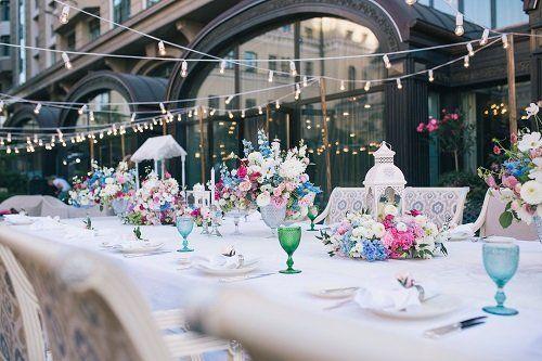 un tavolo apparecchiato e decorato con fiori di color azzurro, rosa e bianco