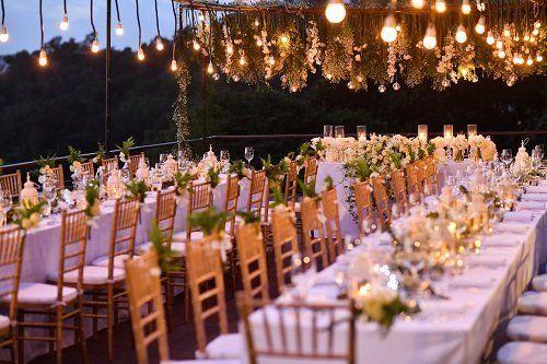 dei tavoli apparecchiati e decorati con dei fiori