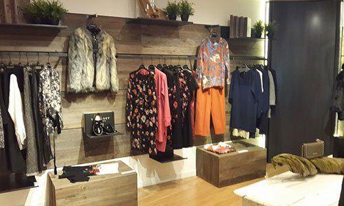 interno di una boutique con abbigliamento da donna appesi su appendiabiti a muro e alcune mensole con vasi di piante