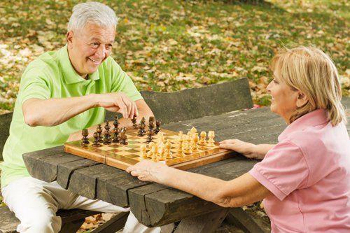 assistenza ad un anziano durante una partita a scacchi