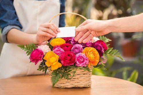 due mani e un cestino di fiori gialli, fucsia e bianchi