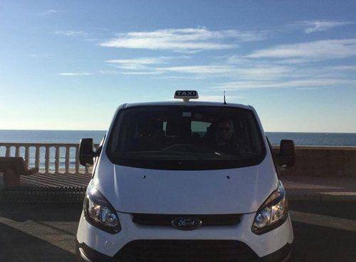 Un taxi a 6 posti, di colore bianco, che sosta in riva al mare
