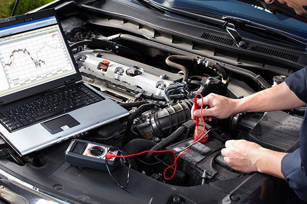 un meccanico con un tester e un computer portatile al lavoro su una vettura con il cofano aperto