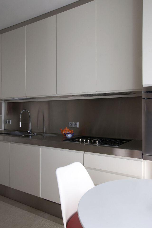 cucina moderna con piastra a induzione e lavabo sulla penisola, 3 vasi di piantine e dietro si intravede la sala da pranzo a Segrate, MI
