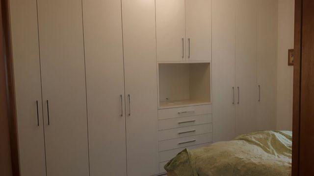 ripostiglio con mensole bianche e parquet in legno a Segrate, MI